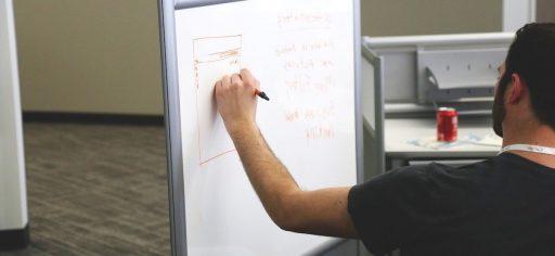 un growth master hacker explicando sus planes en una pizarra para que se le entienda mejor,
